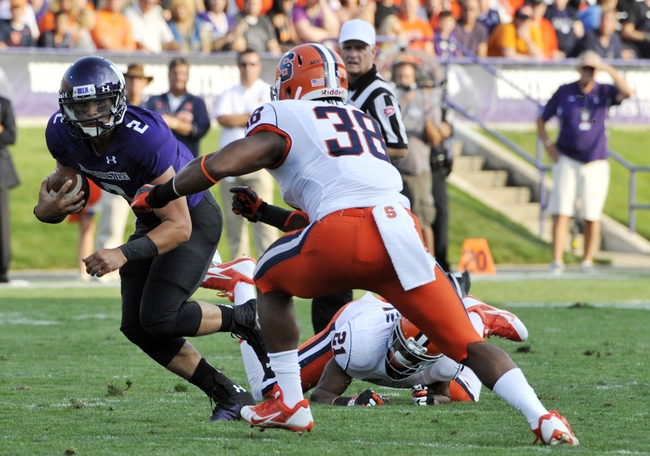 Sep 7, 2013; Evanston, IL, USA; Northwestern Wildcats quarterback Kain Colter (2) tries to run past Syracuse Orange linebacker Cameron Lynch (38) during the first quarter at Ryan Field. Mandatory Credit: David Banks-USA TODAY Sports