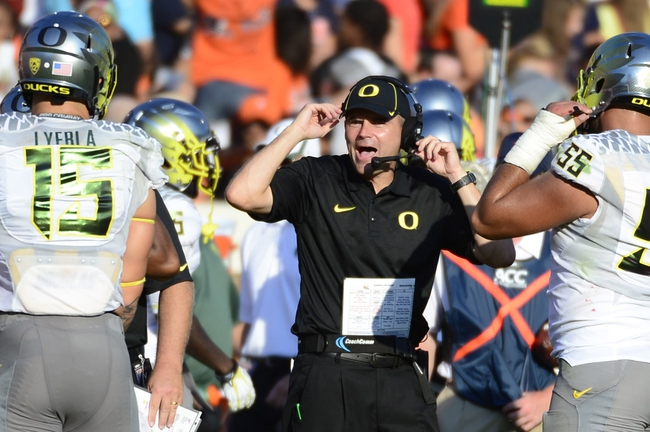 Sep 7, 2013; Charlottesville, VA, USA; Oregon Ducks head coach Mark Helfrich (center) reacts in the second half. The Ducks defeated the Virginia Cavaliers 59-10 at Scott Stadium. Mandatory Credit: Bob Donnan-USA TODAY Sports