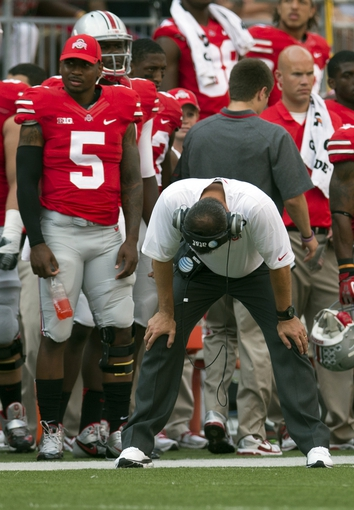 Sep 7, 2013; Columbus, OH, USA; Ohio State Buckeyes head coach Urban Meyer reacts to his team's defensive play against the San Diego State Aztecs as injured quarterback Braxton Miller (5) stands behind him at Ohio Stadium. Ohio State won the game 42-7. Mandatory Credit: Greg Bartram-USA TODAY Sports
