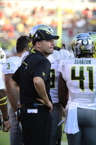 Sep 7, 2013; Charlottesville, VA, USA; Oregon Ducks head coach Mark Helfrich (left) reacts in the fourth quarter. The Ducks defeated the Virginia Cavaliers 59-10 at Scott Stadium. Mandatory Credit: Bob Donnan-USA TODAY Sports