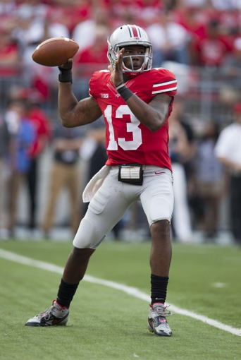 Sep 7, 2013; Columbus, OH, USA; Ohio State Buckeyes quarterback Kenny Guiton (13) fires a pass upfield against the San Diego State Aztecs at Ohio Stadium. Ohio State won the game 42-7. Mandatory Credit: Greg Bartram-USA TODAY Sports