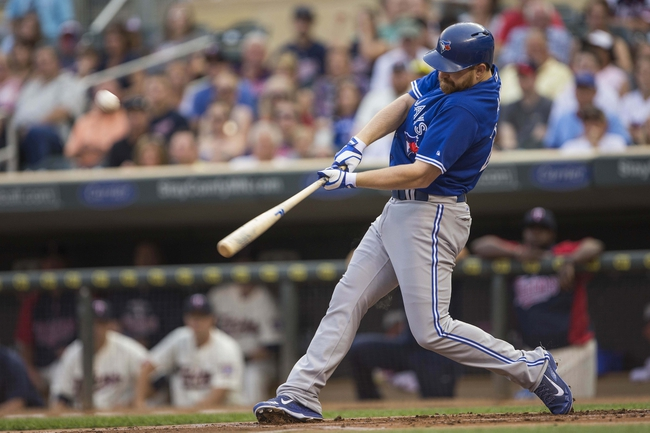 Sep 7, 2013; Minneapolis, MN, USA; Toronto Blue Jays first baseman Adam Lind (26) hits a three run home run in the first inning against the Minnesota Twins at Target Field. Mandatory Credit: Jesse Johnson-USA TODAY Sports