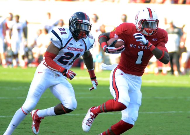 Sep 7, 2013; Raleigh, NC, USA; North Carolina State Wolfpack receiver Marquez Valdes-Scantling (1) runs after a reception as Richmond Spiders defensive back Justin Grant (21) pursues during the first half at Carter Finley Stadium. Mandatory Credit: Rob Kinnan-USA TODAY Sports