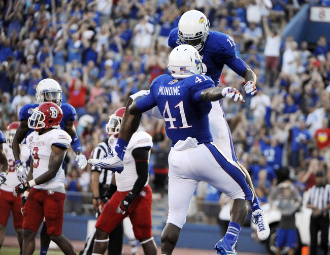 Sep 7, 2013; Lawrence, KS, USA; Kansas Jayhawks wide receiver Justin McCay (19) celebrates with tightened Jimmay Mundine (41) after catching a touchdown pass against the South Dakota Coyotes in the first half at Memorial Stadium. Mandatory Credit: John Rieger-USA TODAY Sports