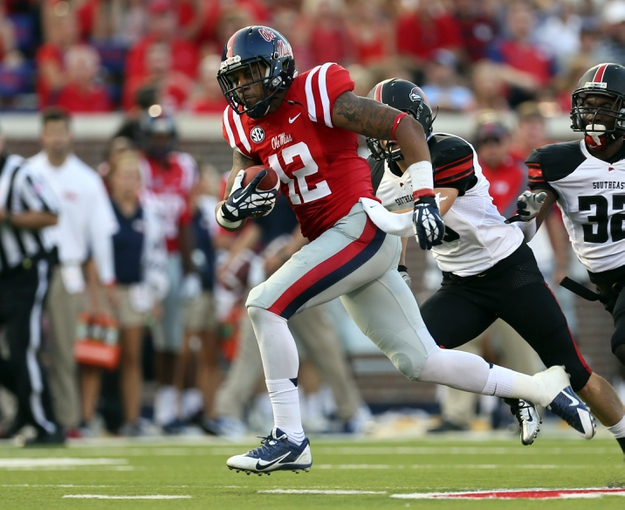 Sep 7, 2013; Oxford, MS, USA; Mississippi Rebels wide receiver Donte Moncrief (12) catches the ball and carries it in for a touchdown during the first half against the Southeast Missouri State Redhawks at Vaught-Hemingway Stadium. Mandatory Credit: Spruce Derden-USA TODAY Sports