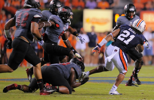 Sep 7, 2013; Auburn, AL, USA; Auburn Tigers running back Tre Mason (21) eludes Arkansas State Red Wolves defense during the first half at Jordan Hare Stadium. Mandatory Credit: Shanna Lockwood-USA TODAY Sports