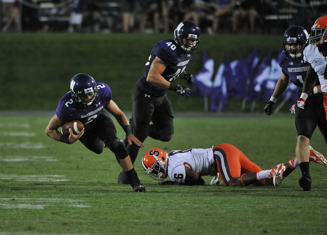 Sep 7, 2013; Evanston, IL, USA; Northwestern Wildcats quarterback Kain Colter (2) is tackled by Syracuse Orange safety Ritchy Desir (6) during the third quarter at Ryan Field. Mandatory Credit: David Banks-USA TODAY Sports
