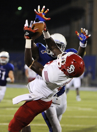 Sep 7, 2013; Lawrence, KS, USA; South Dakota Coyotes wide receiver Tyson Graham Jr. (8) catches a pass against Kansas Jayhawks safety Isaiah Johnson (5) in the second half at Memorial Stadium. Kansas won the game 31-14. Mandatory Credit: John Rieger-USA TODAY Sports