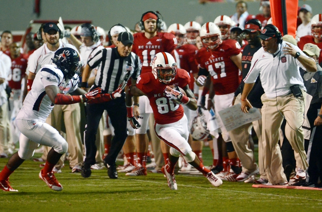 Sep 7, 2013; Raleigh, NC, USA;  North Carolina State Wolfpack receiver Bryan Underwood (80) runs down the sideline after a second half catch as Richmond Spiders defensive back DeShawn Holmes (7) pursues during the second half  at Carter Finley Stadium.  North Carolina State won 23-21. Mandatory Credit: Rob Kinnan-USA TODAY Sports