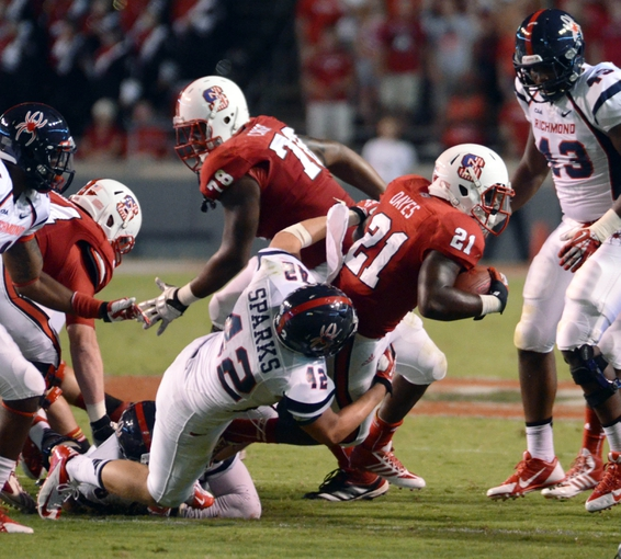 Sep 7, 2013; Raleigh, NC, USA; North Carolina State Wolfpack running back Matt Dayes (21) is tackled by Richmond Spiders linebacker Walt Sparks (42) during the second half at Carter Finley Stadium.  North Carolina State won 23-21. Mandatory Credit: Rob Kinnan-USA TODAY Sports