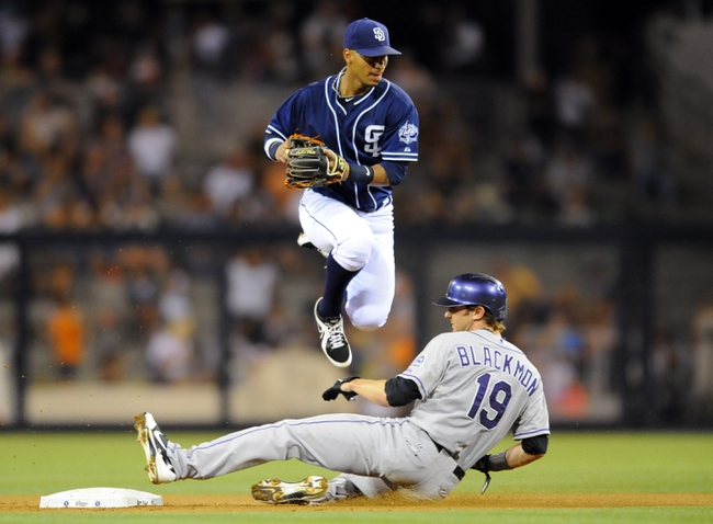Sep 7, 2013; San Diego, CA, USA; San Diego Padres shortstop Ronny Cedeno (3) jumps over a slide by Colorado Rockies center fielder Charlie Blackmon (19) following a force out at second during the eighth inning at Petco Park. Mandatory Credit: Christopher Hanewinckel-USA TODAY Sports