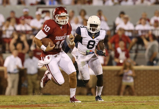 Sep 7, 2013; Norman, OK, USA; Oklahoma Sooners quarterback Blake Bell (10) scrambles on his first play from scrimmage in the fourth quarter against West Virginia Mountaineers safety Karl Joseph (8) at Gaylord Family - Oklahoma Memorial Stadium. The Oklahoma Sooners beat the West Virginia Mountaineers 16-7. Mandatory Credit: Matthew Emmons-USA TODAY Sports