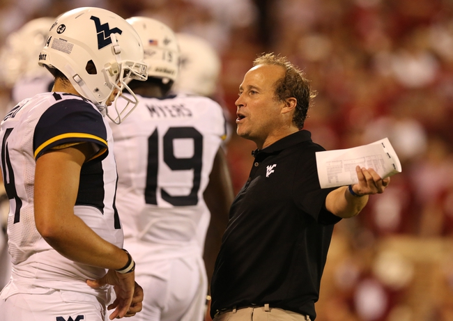 Sep 7, 2013; Norman, OK, USA; West Virginia Mountaineers head coach Dana Holgorsen talks with quarterback Paul Millard (14) during a timeout in the third quarter against the Oklahoma Sooners at Gaylord Family - Oklahoma Memorial Stadium. The Oklahoma Sooners beat the West Virginia Mountaineers 16-7. Mandatory Credit: Matthew Emmons-USA TODAY Sports