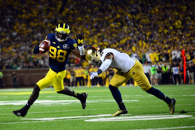 Sep 7, 2013; Ann Arbor, MI, USA; Michigan Wolverines quarterback Devin Gardner (98) scrambles out of the pocket after getting away from Notre Dame Fighting Irish safety Matthias Farley (41) during the fourth quarter at Michigan Stadium. Mandatory Credit: Andrew Weber-USA TODAY Sports