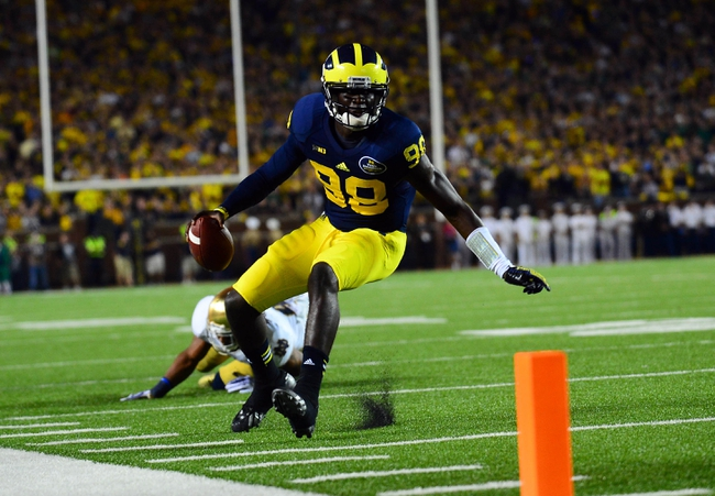 Sep 7, 2013; Ann Arbor, MI, USA; Michigan Wolverines quarterback Devin Gardner (98) scrambles out of the pocket getting away from Notre Dame Fighting Irish safety Matthias Farley (41) during the fourth quarter at Michigan Stadium. Mandatory Credit: Andrew Weber-USA TODAY Sports