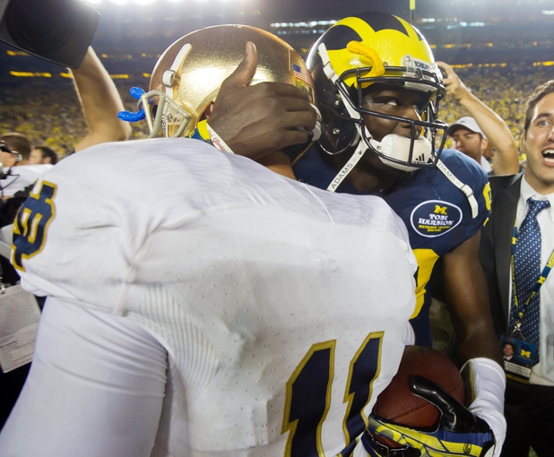 Sep 7, 2013; Ann Arbor, MI, USA; Michigan Wolverines quarterback Devin Gardner (98) hugs Notre Dame Fighting Irish quarterback Tommy Rees (11) after Michigan defeated Notre Dame 41-30 at Michigan Stadium. Mandatory Credit: Matt Cashore-USA TODAY Sports