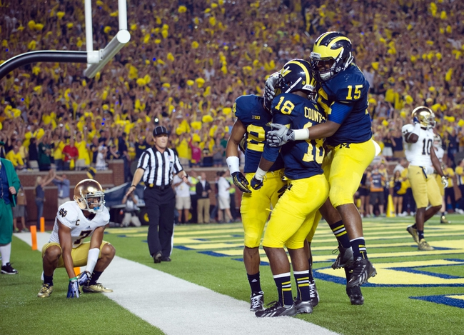 Sep 7, 2013; Ann Arbor, MI, USA; Michigan Wolverines defensive back Blake Countess (18) celebrates with linebacker James Ross III (15) and defensive back Delonte Hollowell (24) after intercepting a pass intended for Notre Dame Fighting Irish wide receiver Chris Brown (2) in the fourth quarter at Michigan Stadium. Michigan won 41-30. Mandatory Credit: Matt Cashore-USA TODAY Sports
