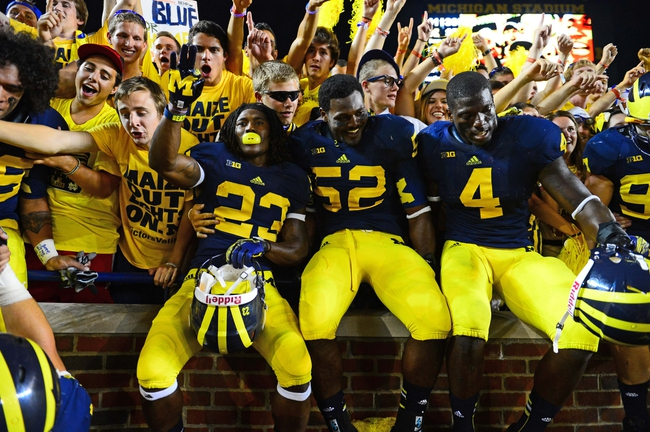 Sep 7, 2013; Ann Arbor, MI, USA; Michigan Wolverines wide receiver Dennis Norfleet (23), linebacker Royce Jenkins-Stone (52) and linebacker Cameron Gordon (4) celebrate in the students section after defeating the Notre Dame Fighting Irish 41-30 at Michigan Stadium. Mandatory Credit: Andrew Weber-USA TODAY Sports