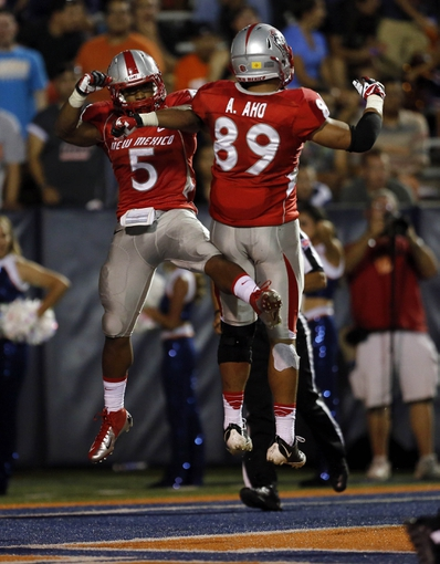 Sep 7, 2013; El Paso, TX, USA; New Mexico Lobos running back Kasey Carrier (5) celebrates with teammate Andrew Aho (89) after scoring a touchdown against the UTEP Miners defense during the second half at Sun Bowl Stadium. The Lobos beat the Miners 42-35 in overtime. Mandatory Credit: Ivan Pierre Aguirre-USA TODAY Sports