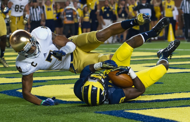 Sep 7, 2013; Ann Arbor, MI, USA; Michigan Wolverines defensive back Blake Countess (18) intercepts a pass intended for Notre Dame Fighting Irish wide receiver TJ Jones (7) in the fourth quarter at Michigan Stadium. Michigan won 41-20. Mandatory Credit: Matt Cashore-USA TODAY Sports