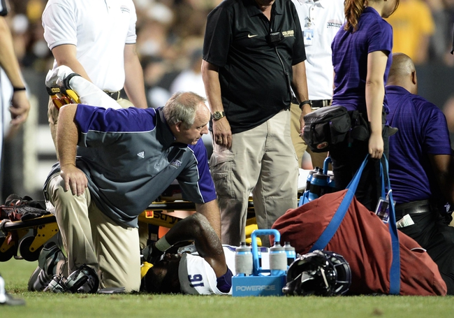 Sep 7, 2013; Boulder, CO, USA; Central Arkansas Bears head coach Clint Conque checks on linebacker Aum'Arie Wallace (16) after an injury to his left leg in the third quarter against the Colorado Buffaloes at Folsom Field. The Buffaloes defeated the Bears 38-24. Mandatory Credit: Ron Chenoy-USA TODAY Sports