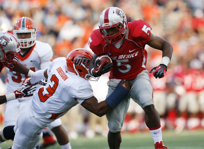 Sep 7, 2013; El Paso, TX, USA; New Mexico Lobos running back Kasey Carrier (5) tries to break free from UTEP Miners defensive back Traun Roberson (3) at Sun Bowl Stadium. The Lobos beat the Miners 42-35 in overtime. Mandatory Credit: Ivan Pierre Aguirre-USA TODAY Sports