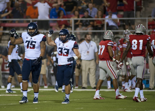 Sep 7, 2013; Las Vegas, NV, USA; Arizona Wildcat defensive linebacker Kirifi Taula, left, and linebacker Jake Fischer celebrate after stopping the UNLV Rebels on a fourth down attempt during an NCAA football game at Sam Boyd Stadium. Mandatory Credit: Stephen R. Sylvanie-USA TODAY Sports