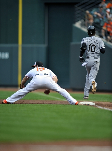 Sep 8, 2013; Baltimore, MD, USA; Chicago White Sox shortstop Alexei Ramirez (10) reaches first base safely on an infield single as Baltimore Orioles first baseman Chris Davis (19) does not get the throw in time at Oriole Park at Camden Yards. Mandatory Credit: Joy R. Absalon-USA TODAY Sports