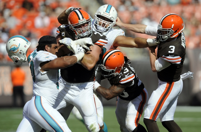 Sep 8, 2013; Cleveland, OH, USA; Cleveland Browns quarterback Brandon Weeden (3) has his face mask grabbed by Miami Dolphins defensive end Jared Odrick (98) as Cleveland Browns tackle Joe Thomas (73) and Cleveland Browns running back Trent Richardson (33) try to block Miami Dolphins defensive end Olivier Vernon (50) during the fourth quarter at FirstEnergy Stadium. Mandatory Credit: Ken Blaze-USA TODAY Sports