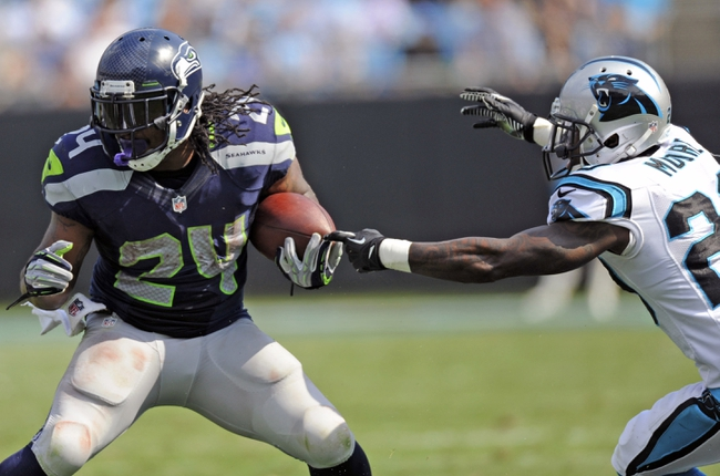 Sep 8, 2013; Charlotte, NC, USA; Seattle Seahawks running back Marshawn Lynch (24) moves the ball as he is purseued by cornerback D.J. Moore (20) during the game at Bank of America Stadium. Seattle wins 12-7. Mandatory Credit: Sam Sharpe-USA TODAY Sports