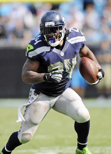 Sep 8, 2013; Charlotte, NC, USA; Seattle Seahawks running back Marshawn Lynch (24) moves the ball during the game against the Carolina Panthers at Bank of America Stadium. Seattle wins 12-7. Mandatory Credit: Sam Sharpe-USA TODAY Sports