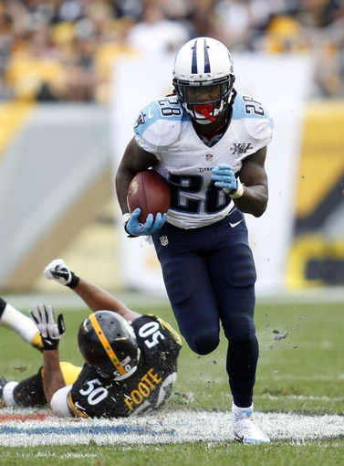 Sep 8, 2013; Pittsburgh, PA, USA; Tennessee Titans running back Chris Johnson (28) carries the ball past Pittsburgh Steelers inside linebacker Larry Foote (50) during the fourth quarter at Heinz Field. The Tennessee Titans won 16-9. Mandatory Credit: Charles LeClaire-USA TODAY Sports