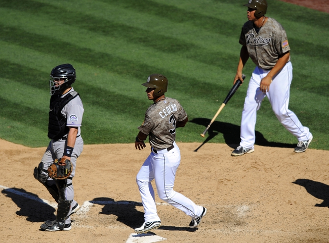 Sep 8, 2013; San Diego, CA, USA; San Diego Padres shortstop Ronny Cedeno (3) and Padres first baseman Kyle Blanks (88) score on a double by Padres catcher Nick Hundley (not pictured) during the seventh inning against the Colorado Rockies at Petco Park. Mandatory Credit: Christopher Hanewinckel-USA TODAY Sports