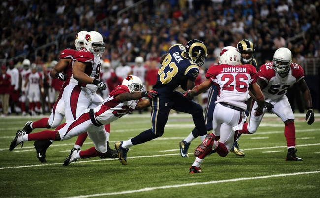 Sep 8, 2013; St. Louis, MO, USA; St. Louis Rams wide receiver Brian Quick (83) catches a 16 yard pass as Arizona Cardinals cornerback Jerraud Powers (25) and Rashad Johnson (26) defend during the second half at Edward Jones Dome. St. Louis defeated Arizona 27-24. Mandatory Credit: Jeff Curry-USA TODAY Sports