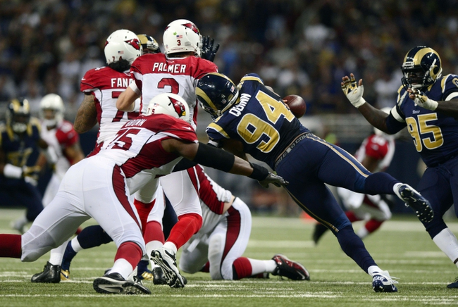 Sep 8, 2013; St. Louis, MO, USA; St. Louis Rams defensive end Robert Quinn (94) knocks the ball from Arizona Cardinals quarterback Carson Palmer (3) hand and forces a fumble during the second half at Edward Jones Dome. St. Louis defeated Arizona 27-24. Mandatory Credit: Jeff Curry-USA TODAY Sports