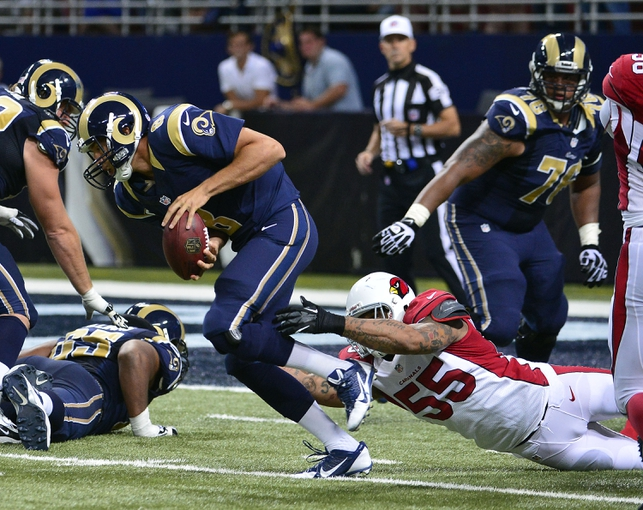Sep 8, 2013; St. Louis, MO, USA; St. Louis Rams quarterback Sam Bradford (8) attempts to scramble away from Arizona Cardinals defensive end John Abraham (55) during the second half at Edward Jones Dome. The Rams defeated the Cardinals 27-24. Mandatory Credit: Scott Rovak-USA TODAY Sports