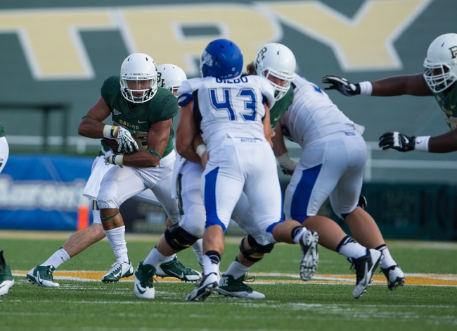 Sep 7, 2013; Waco, TX, USA; Baylor Bears running back Shock Linwood (32) rushes past Buffalo Bulls linebacker Nick Gilbo (43) during the game at Floyd Casey Stadium. The Bears defeated the Bulls 70-13. Mandatory Credit: Jerome Miron-USA TODAY Sports