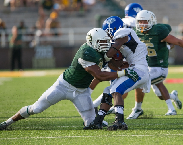 Sep 7, 2013; Waco, TX, USA; Baylor Bears defensive end Shawn Oakman (2) tackles Buffalo Bulls running back James Potts (1) during the game at Floyd Casey Stadium. The Bears defeated the Bulls 70-13. Mandatory Credit: Jerome Miron-USA TODAY Sports