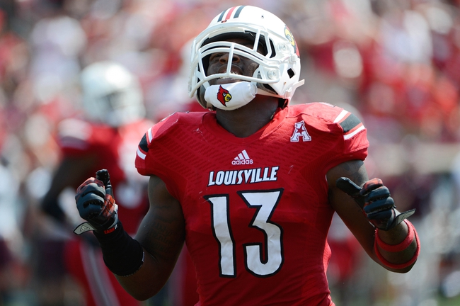 Sep 7, 2013; Louisville, KY, USA; Louisville Cardinals linebacker James Burgess (13) reacts during the second quarter against Eastern Kentucky Colonels at Papa John's Cardinal Stadium. Louisville defeated Eastern Kentucky 44-7.  Mandatory Credit: Jamie Rhodes-USA TODAY Sports