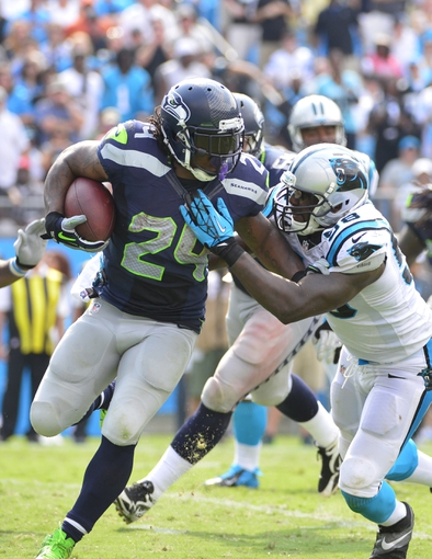 Sep 8, 2013; Charlotte, NC, USA; Seattle Seahawks running back Marshawn Lynch (24) runs as Carolina Panthers outside linebacker Thomas Davis (58) defends in the fourth quarter. The Seahawks defeated the Panthers 12-7 at Bank of America Stadium. Mandatory Credit: Bob Donnan-USA TODAY Sports