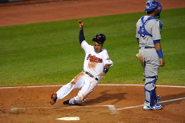 Sep 9, 2013; Cleveland, OH, USA; Cleveland Indians third baseman Jose Ramirez (left) scores a run on an error beside Kansas City Royals catcher Salvador Perez (13) in the third inning at Progressive Field. Mandatory Credit: David Richard-USA TODAY Sports