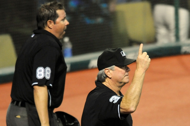 Sep 9, 2013; Cleveland, OH, USA; First base umpire Dana DeMuth (right) signals a home run beside home plate umpire Doug Eddings (88) in the seventh inning at Progressive Field. After a video review DeMuth overturned his call on a foul ball hit by Cleveland Indians designated hitter Carlos Santana (not pictured) in a game against the Kansas City Royals. Mandatory Credit: David Richard-USA TODAY Sports