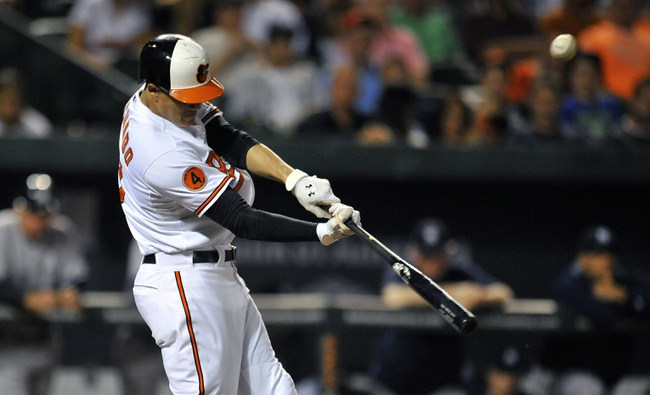 Sep 9, 2013; Baltimore, MD, USA; Baltimore Orioles third baseman Manny Machado (13) doubles in the seventh inning against the New York Yankees at Oriole Park at Camden Yards. The Orioles defeated the Yankees 4-2. Mandatory Credit: Joy R. Absalon-USA TODAY Sports