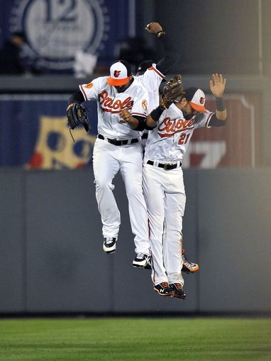 Sep 9, 2013; Baltimore, MD, USA; Baltimore Orioles outfielders Chris Dickerson (left), Nick Markakis (right) and Adam Jones (rear) celebrate after a game against the New York Yankees at Oriole Park at Camden Yards. The Orioles defeated the Yankees 4-2. Mandatory Credit: Joy R. Absalon-USA TODAY Sports