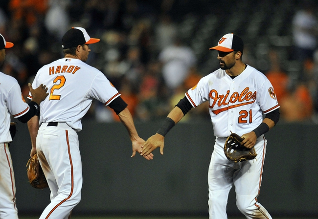 Sep 9, 2013; Baltimore, MD, USA; Baltimore Orioles teammates J.J. Hardy (2) and Nick Markakis (21) celebrate after a game against the New York Yankees at Oriole Park at Camden Yards. The Orioles defeated the Yankees 4-2. Mandatory Credit: Joy R. Absalon-USA TODAY Sports