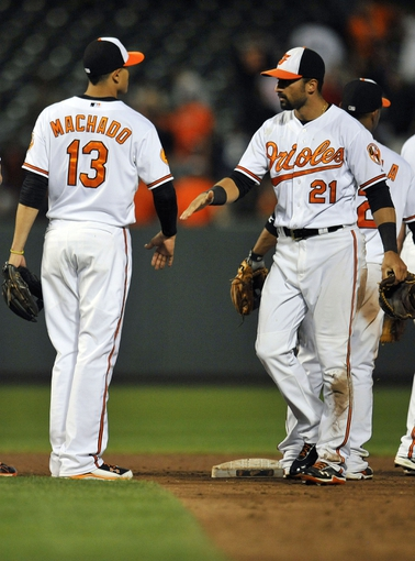 Sep 9, 2013; Baltimore, MD, USA; Baltimore Orioles teammates Manny Machado (13) and Nick Markakis (21) celebrate after a game against the New York Yankees at Oriole Park at Camden Yards. The Orioles defeated the Yankees 4-2. Mandatory Credit: Joy R. Absalon-USA TODAY Sports