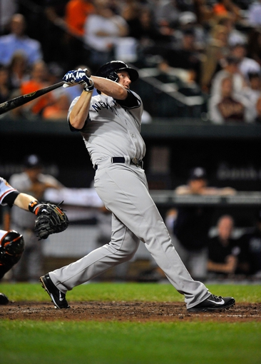 Sep 9, 2013; Baltimore, MD, USA; New York Yankees first baseman Lyle Overbay (55) hits a solo home run in the seventh inning against the Baltimore Orioles at Oriole Park at Camden Yards. The Orioles defeated the Yankees 4-2. Mandatory Credit: Joy R. Absalon-USA TODAY Sports