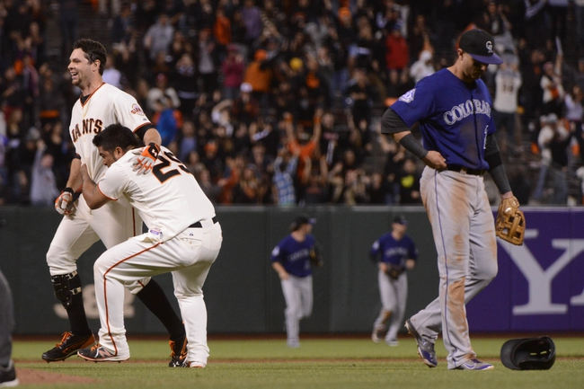September 9, 2013; San Francisco, CA, USA; San Francisco Giants first baseman Brandon Belt (9, left) is congratulated by catcher Hector Sanchez (29) for hitting a walk-off RBI-single to score center fielder Angel Pagan (16, not pictured) against Colorado Rockies shortstop Troy Tulowitzki (2, right) at AT&T Park. The Giants defeated the Rockies 3-2 in 10 innings. Mandatory Credit: Kyle Terada-USA TODAY Sports
