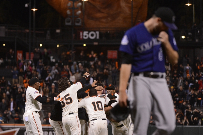 September 9, 2013; San Francisco, CA, USA; San Francisco Giants first baseman Brandon Belt (9) is congratulated by his team after hitting a walk-off RBI-single to score center fielder Angel Pagan (16, not pictured) against Colorado Rockies pitcher Adam Ottavino (0, right) during the 10th inning at AT&T Park. The Giants defeated the Rockies 3-2 in 10 innings. Mandatory Credit: Kyle Terada-USA TODAY Sports