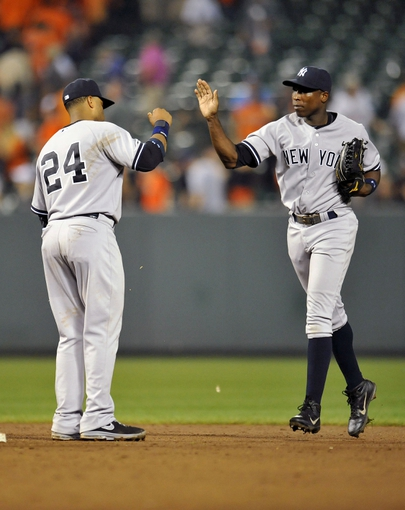 Sep 10, 2013; Baltimore, MD, USA; New York Yankees teammates Robinson Cano (left) and Alfonso Soriano (right) celebrate after a game against the Baltimore Orioles at Oriole Park at Camden Yards. The Yankees defeated the Orioles 7-5. Mandatory Credit: Joy R. Absalon-USA TODAY Sports